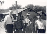 Sonny Montgomery poses with others in front of wooden complex